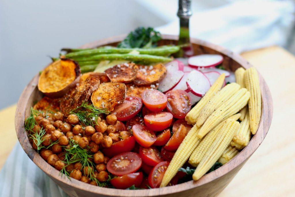 Kale salad with sweet potato, radish, green beans, baby corn, and tomato